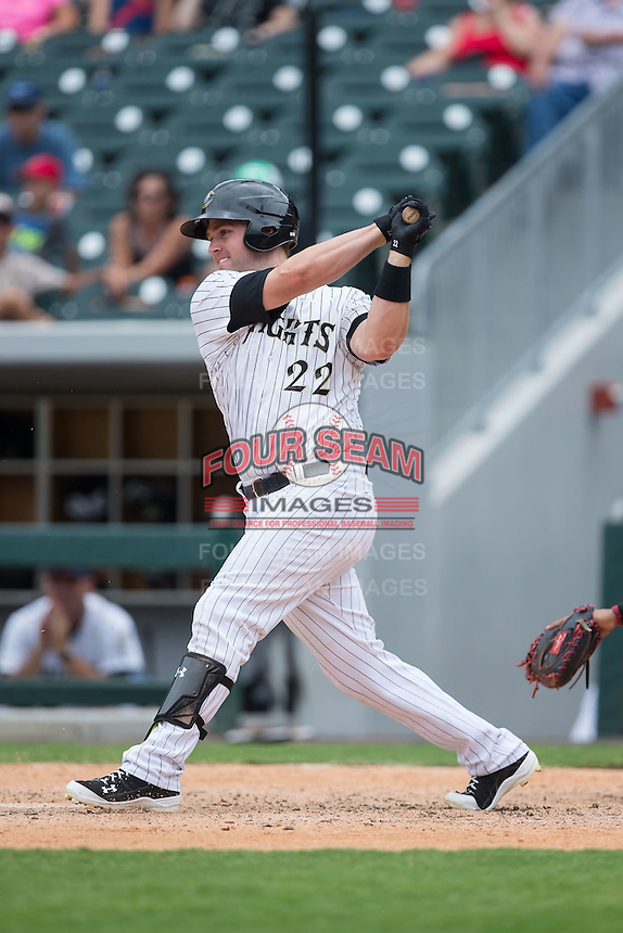 Matt Davidson (22) of the Charlotte Knights follows through on his swing against the Gwinnett Braves at BB&T BallPark on July 3, 2015 in Charlotte, North Carolina.  The Braves defeated the Knights 11-4 in game one of a day-night double header.  (Brian Westerholt/Four Seam Images)