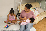 newborn baby girl one month old  Mexican American fed nursed by mother as older sister age 3 looks at a picture book horizontal