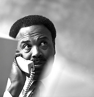 African-American businessman at work, talking on phone while sitting at desk with computer; technology; problem-solver; conversation; professional, occupations, Black man, black and white image; 4x5 original. Dave Johnson.