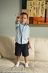 3 year old boy standing on couch at home holding up three fingers to show his age