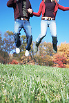 USA, Pennsylvania, Doylestown, low section of teenage couple (16-17) holding hands and jumping in park