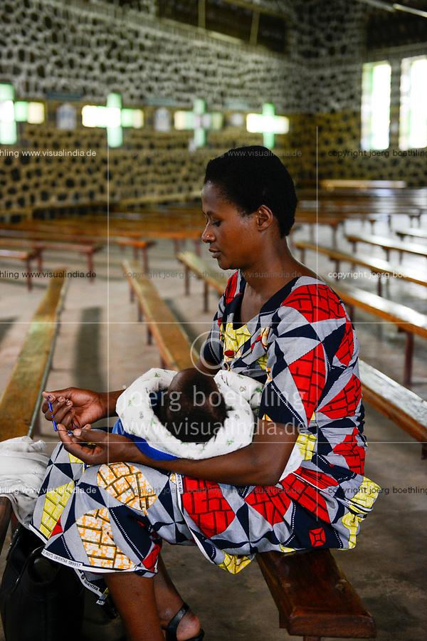 RWANDA, Ruhengeri, village Busogo, woman with baby praying a rosary in church / RUANDA, Frau mit Kleinkind in Kirche Busogo