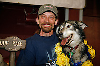 "2007 Iditarod champion Lance Mackey and his lead dog ""Larry"" with champion roses around his neck at the Nome awards banquet."