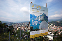 Switzerland. Canton Ticino. Aldesago. Real estate billboard. Flats for sale. Construction of houses with flats on deluxe standing. View on the city of Lugano. Aldesago is distant 5 km from Lugano. 2.06.12 © 2012 Didier Ruef