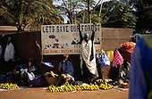 Banjul, The Gambia. People selling fruit on the street below a sign which says 'Let's Save Our Forests'.