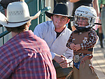 Weston Starr, 2, of Fallon waits with his uncle Blaine Tibbals for the start of the mutton bustin' event at the Smackdown Tour at Fuji Park in Carson City, Nev., on Saturday, June 7, 2014.<br />