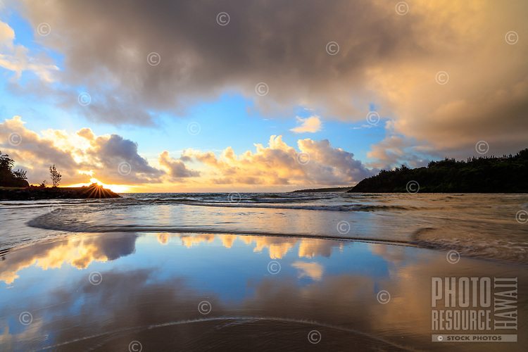 Sunrise is mirrored in the waters at Kahili (or Rock Quarries or Rock Quarry) Beach in Kilauea, Kaua'i.