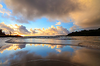 Sunrise is mirrored in the waters at Kahili (or Rock Quarries or Rock Quarry) Beach in Kilauea, Kaua'i.