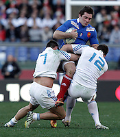 Rugby, torneo Sei Nazioni 2013: Italia vs Francia. Roma, stadio Olimpico, 3 febbraio 2013..France's Florian Fritz, center, is tackled by Italy's Simone Favaro, left, and Alberto Sgarbi, during the Six Nations rugby union international match between Italy and France, at Rome's Olympic stadium, 3 February 2013..UPDATE IMAGES PRESS/Riccardo De Luca