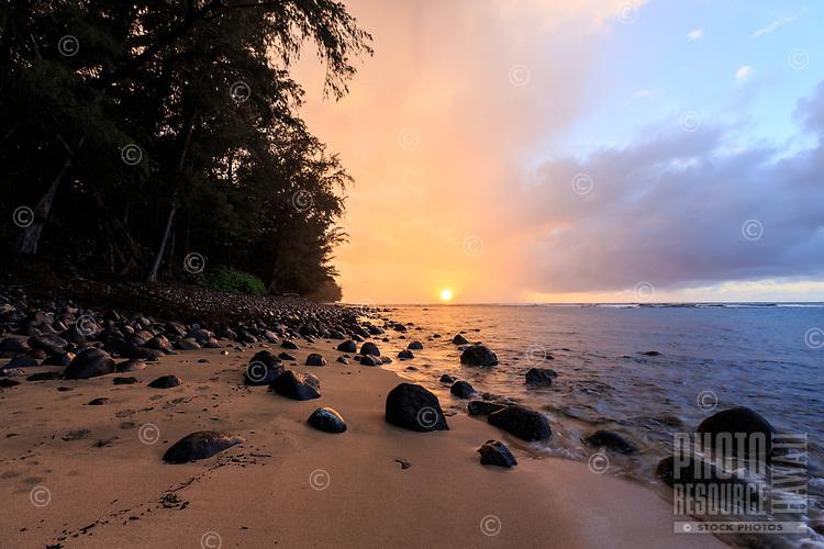 The sun sets through the mist and rain on a rock-strewn sandy beach between Ke'e and Ha'ena Beach Parks on Kaua'i.