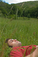 Man laying on back in grassy field