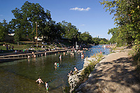 Swimmers frolic, float and swim in Barton Springs Pool during a hot summer's day at Zilker Park in Austin, Texas.