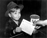 An eager school boy gets his first experience in using War Ration Book Two.  With many parents engaged in war work, children are being taught the facts of point rationing for helping out in family marketing.  February 1943.  Alfred Palmer. (OWI)<br /> Exact Date Shot Unknown<br /> NARA FILE #:  208-AA-322H-1<br /> WAR & CONFLICT #:  792