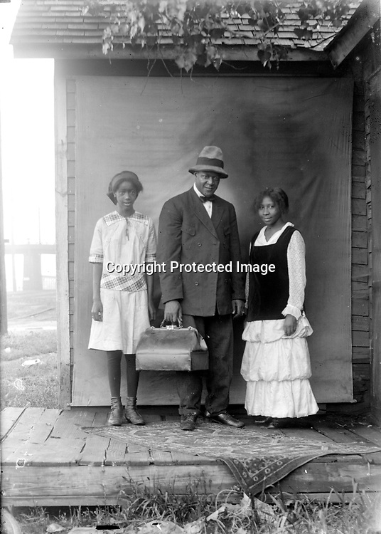 FLORENCE JONES, KIT CARRIGER, AND A GENTLEMAN<br /> Florence Jones (left) and Kit Carriger pose with an unidentified man before Johnson's portable backdrop. Perhaps the man was a traveler, but if the satchel is a medical bag, then he may have been Dr. Harrison A. Longdon, one of two black physicians who served Lincoln's African American community in this era. Longdon was in Lincoln from the mid 1910s to 1916, overlapping for those years with Dr. Arthur B. Moss, who served from the mid 1910s until his death in 1938. Serving a small and impoverished community was not a path to wealth--both Longdon and Moss lived in rented quarters.<br /> <br /> Photographs taken on black and white glass negatives by African American photographer(s) John Johnson and Earl McWilliams from 1910 to 1925 in Lincoln, Nebraska. Douglas Keister has 280 5x7 glass negatives taken by these photographers. Larger scans available on request.