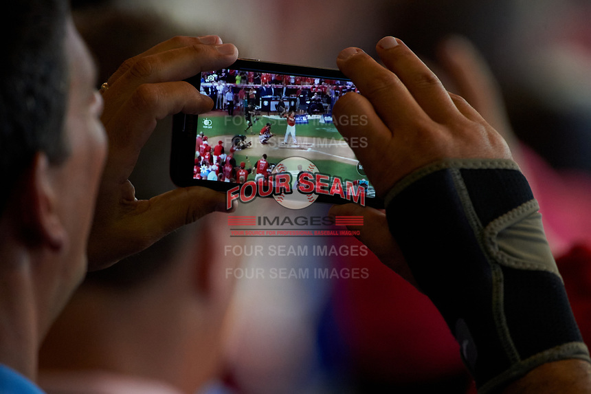 A fan uses his phone to record the MLB Home Run Derby on July 13, 2015 at Great American Ball Park in Cincinnati, Ohio.  (Mike Janes/Four Seam Images)