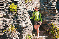 A young woman amongst limestone formations in Punakaiki - Paparoa National Park, West Coast, New Zealand