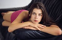 Woman laying on couch looking at camera<br />