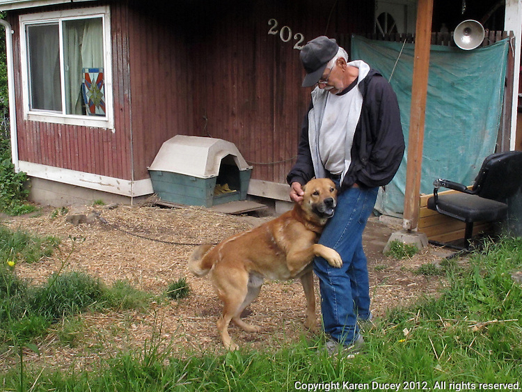 Sonny, a chaind dog in Tacoma, Washington with Walter, a neighbor, who feeds him.  Walter said his daughter used to live in the house but moved to Florida and abandoned the dog.