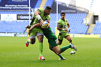 Luther Burrell of Northampton Saints offloads in the tackle during the Premiership Rugby match between London Irish and Northampton Saints at the Madejski Stadium on Saturday 4th October 2014 (Photo by Rob Munro)