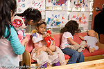 Preschool Headstart 3-5 year olds isolated girl standing at edge of group of girls doing pretend play in family area