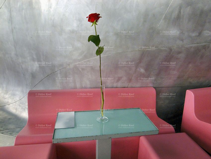 France. Department Ile-de-France. Paris. Centre national d'art et de culture Georges-Pompidou. Interior design. Modern pink furniture. A red rose on a table in the restaurant of the Centre Georges Pompidou. The Pompidou Centre,  is a complex in the Beaubourg area of the 4th arrondissement of Paris, near Les Halles, It was designed in the style of high-tech architecture and houses the Musée National d'Art Moderne which is the largest museum for modern art in Europe. Because of its location, the Centre is known locally as the Beaubourg. 09.07.2011 © 2011 Didier Ruef