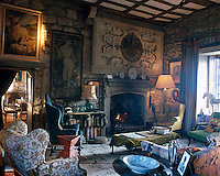 The exposed rough stone walls of the living room are partly concealed behind a few large paintings and a carved overmantel