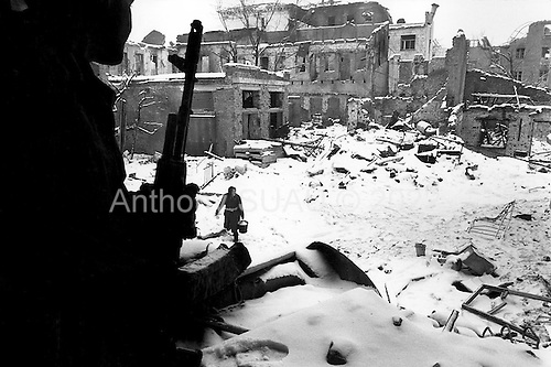 Grozny, Chechyna.January 1995.In the destroyed center of Grozny a Russian soldier looks down from a bombed building at a woman who lives in her basement near by. She has come out to take snow to melt into drinking and cooking water.