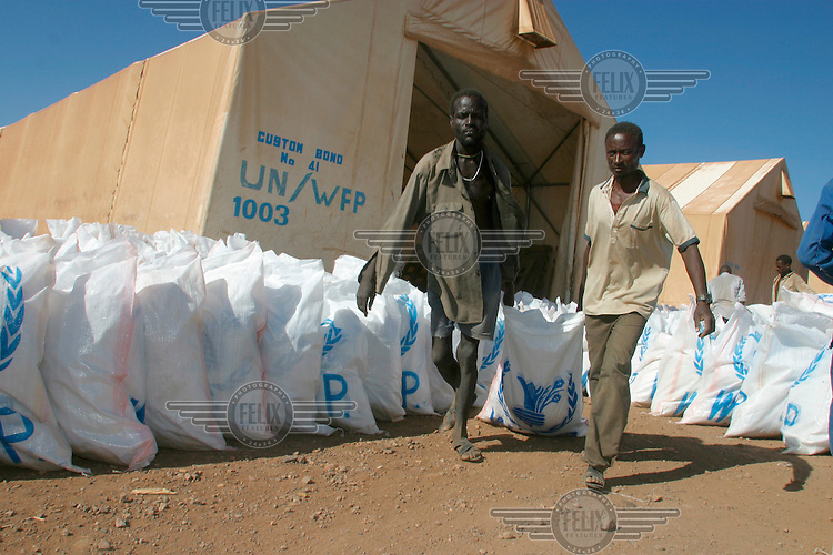 Bags of food being loaded on to transport planes at Logichoggio airport. The planes, operated by the United Nations World Food Programme (UN WFP), fly over Southern Sudan dropping food aid. The civil war has displaced the civilian population and created constant food shortages.