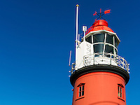 red lighthouse against a clear blue sky