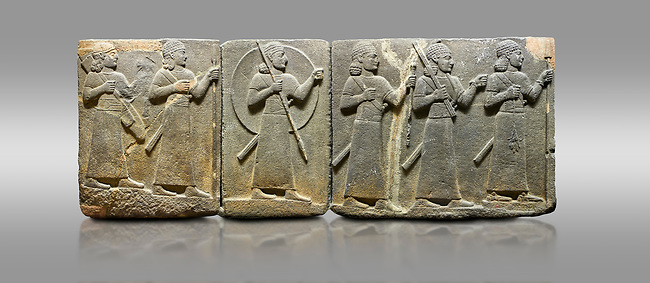 Picture & image of Hittite relief sculpted orthostat stone panel of Royal Buttress Basalt, Karkamıs, (Kargamıs), Carchemish (Karkemish), 900-700 B.C. Warriors. Anatolian Civilisations Museum, Ankara, Turkey.<br /> <br /> Right panel - Three figures each with a long dress, a thick belt and curly hair. The figure in front holds a spear with a broken tip in his left hand and a leafy branch in his right hand. The figure in the middle made his left hand a fist, and he carries a tool with his right hand at the level of his head. They are followed with a figure holding a sceptre in his left hand. All three have each a long sword at their waist. <br /> <br /> Against a gray background.