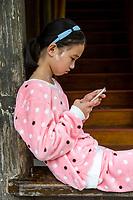 Linkeng, Zhejiang, China.  Teenage Girl Using her Cell Phone.