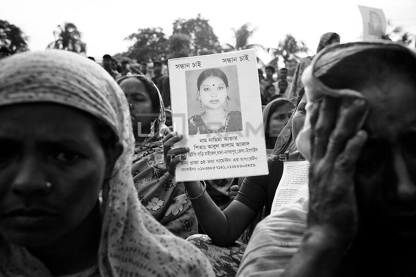 During a protest, Bangladeshi women hold photos of their missing relatives at the site of Rana Plaza building collapse. Savar, near Dhaka, Bangladesh