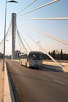 The Millennium Bridge is a cable stayed bridge that spans Moraca River with cables that form a graphic pattern and a single central supporting column. Commuter bus. Podgorica capital. Montenegro, Balkan, Europe. Designed by Mladen Ulicevic.