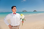 Asian groom waits for his bride with a bouquet of flowers during a stroll on Lanikai beach as they look forward to their life as a married couple following their wedding.