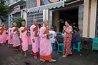 female novices collecting alms, early morning<br /> Yangon on a sunny day of July 2017