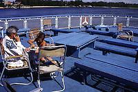 RUSSIA, viaggio in battello da San Pietroburgo a Mosca lungo il Volga. Nell'immagine un uomo e un ragazzino sul ponte del battello giocano a scacchi. Sullo sfondo il paesaggio delle rive del fiume, alberi e case.