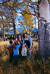 A family of five play under fall-colored aspen trees in Rocky Mtn Nat'l Park, CO.