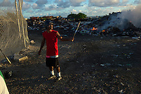 A softball player warms up before batting on a makeshift baseball field in the middle of the garbage dump on Ebeye island, Kwajalein Atoll on June 21, 2012. Over 12,000 people live on the tiny overcrowded island of 36 hectares. The islanders relocated to Ebeye from their original homes because the U.S. military leases those areas for ballistic missile testing. Other current residents of Ebeye moved from islands which were contaminated by U.S. nuclear bomb tests. Infrastructure, housing and sanitation on Ebeye are deplorable, and there is not enough space for a normal baseball field. The neighboring U.S. military base has three large softball fields which are rarely used.