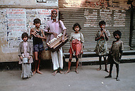 Children beg and perform for money on the streets of Calcutta, India - Child labor as seen around the world between 1979 and 1980 - Photographer Jean Pierre Laffont, touched by the suffering of child workers, chronicled their plight in 12 countries over the course of one year.  Laffont was awarded The World Press Award and Madeline Ross Award among many others for his work.