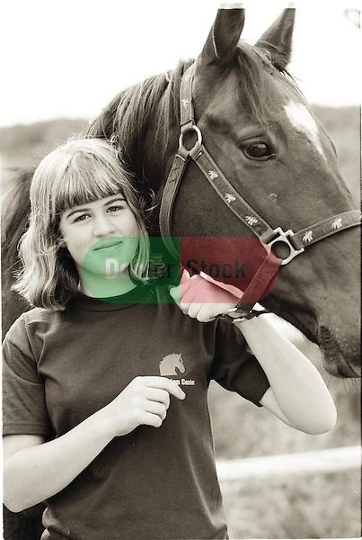 Portrait of healthy teenage girl holding halter of horse