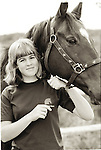 Portrait of healthy teenage girl holding halter of horse