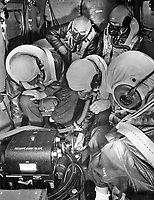 Students receiving familiarization with flight photography at Chevalier Field.  Checking with high altitude equipment installed in plane.  Note that on this check they are not wearing gloves, whereas as high altitude work they would have to wear gloves, when handling exposed metal object that are not heated for use.
