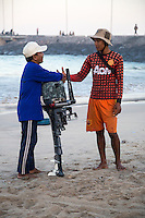 Jimbaran, Bali, Indonesia.  Two Fishermen Greeting one Another on the Beach, Early Morning.