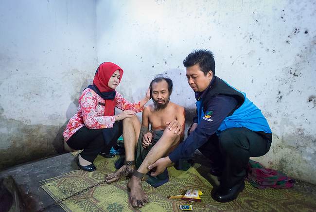 """5 April 2017, Surabaya,East Java,Indonesia: Ubaidilah a 44 year old mental illness sufferer is released from the chains he has been shackled to in a dingy room next to his family home in Badal Pandean village, East Java. Indonesian Social Affairs Dept. workers cut the bonds, cut his hair and nails and washed his emaciated body before putting him in a strait jacket and taking him to a facility in Malang for treatment. Ubaidilah is a patient in a program called """"E- Shackling"""" which aims to free people suffering from mental illness, from the shackles that family often place them in to control them in the wake of a lack of treatment options and the program will treat them and enter them in a data base allowing them to be traced before releasing them back to their families. Some people stay chained to a stake or in rooms for years by their families and not all families are willing to take their sick family members back. Picture by Graham Crouch/The Australian"""