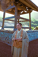The headmaster of a Zen Buddhist temple stands in front of the temple bell.