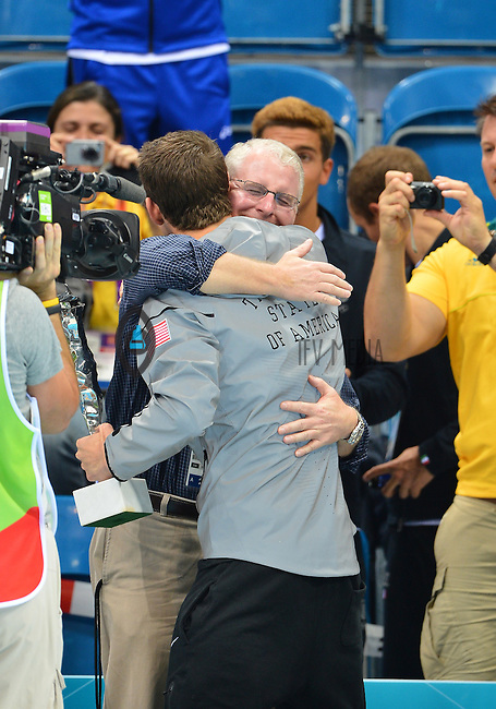 """August 04, 2012..Michael Phelps is embraced by his Coach Bob Bowman after he was awarded """"The Greatest Olympic Athlete of All Times"""" trophy by FINA at the Aquatics Center on day eight of 2012 Olympic Games in London, United Kingdom."""