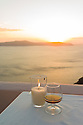 Santorini, Greece. 09.05.2012. Table with candle and glass of Metaxa brandy, overlooking the Caldera, at sunset in Fira, Santorini. Photograph © Jane Hobson.