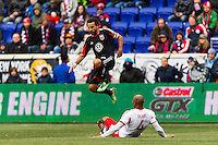 Dwayne De Rosario (7) of D. C. United jumps over a tackle by Jamison Olave (4) of the New York Red Bulls during the first half of a Major League Soccer (MLS) match at Red Bull Arena in Harrison, NJ, on March 16, 2013.