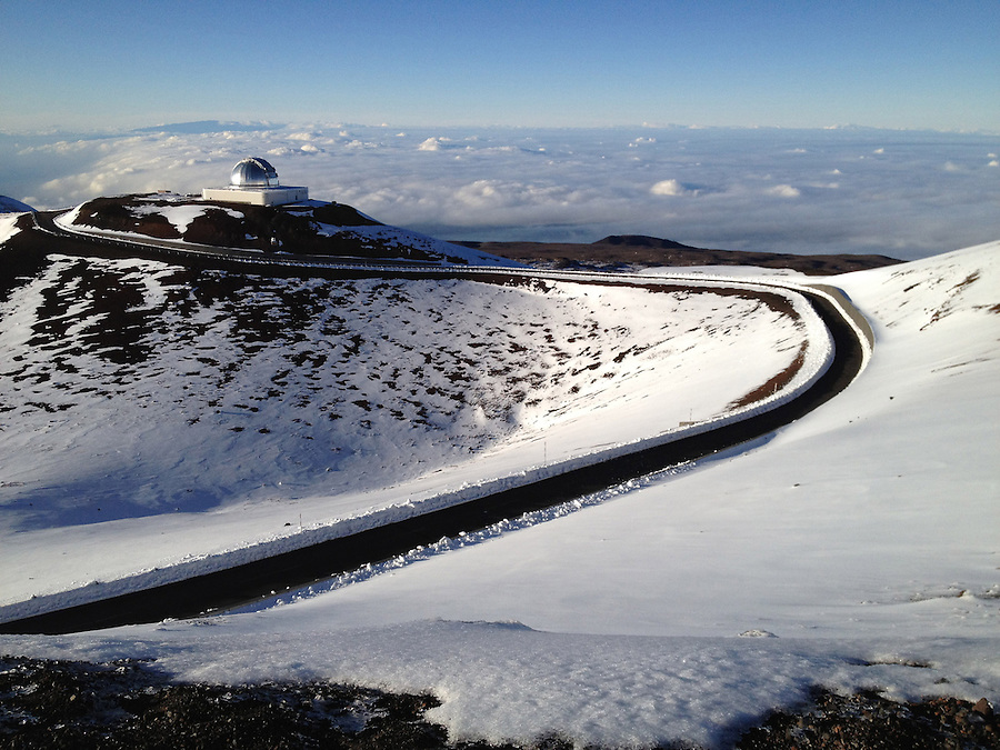 Above the clouds, snow covers the top of Mauna Kea on the Big Island of Hawaii. Mauna Kea is 13,796ft high but from from the bottom of the ocean, is the tallest mountain in the world at 33,500ft.  Due to its high altitude, dry environment and isolated geographical location, Mauna Kea's summit is one of the best sites in the world for astronomical observation. Since the creation of an access road in 1964, thirteen telescopes funded by eleven countries have been constructed at the summit.