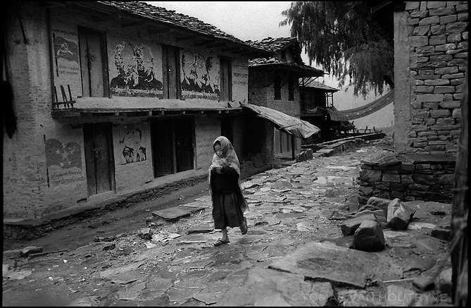 A young girl walks through the rain past a wall painted with images of Marx, Engels, Lenin, Stalin and Mao in Thabang, the capital of Nepal's Maoist held areas on Monday, 20 June 2005. The rebels have decorated the entire town with communist symbols, flags and images of revolutionaries.<br />